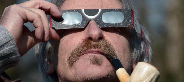 un-homme-regarde-l-eclipse-solaire-partielle-a-travers-des-lunettes-de-protection-le-20-mars-2015_5305185